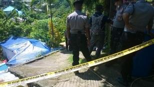 Polisi membentangkan police line di lokasi makam Yanes Balubun